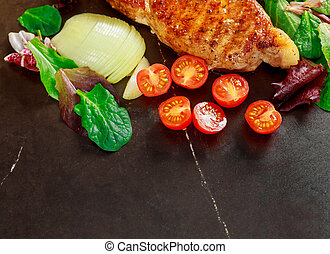 Grilled steak meat with vegetables on stone board, top view