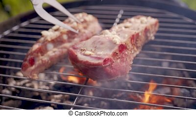 Grilled steak. Ribs on barbecue grill. Cooking pork ribs on...