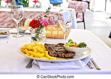 Grilled steak with french fries and vegetables on a white table outdoors. Fresh served
