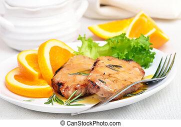 Grilled steak with orange sauce on white plate