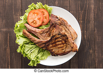 Grilled steak with vegetables on a wooden background.