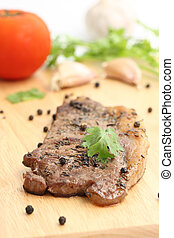 Grilled steak with vegetables on wood background