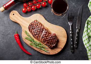 Grilled striploin steak and red wine over stone table. Top ...
