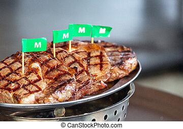Grilled striploin steak arranged in a metal tray.
