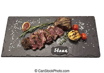 Grilled striploin steak on a stone plate baked potatoes and ...