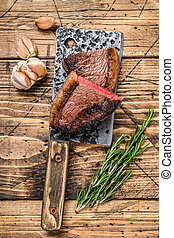 Grilled top sirloin cap beef meat steak on a cleaver. wooden background. Top view