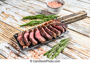 Grilled top sirloin cap or picanha steak on a meat cleaver with herbs. White wooden background. Top view