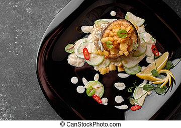 Grilled trout fillet with vegetables, on black background