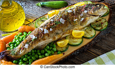 Grilled trout fillets with vegetables on wooden background