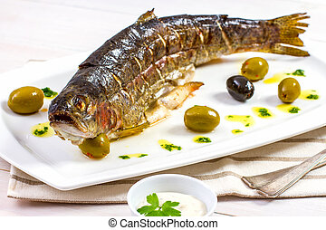 Grilled trout with olive on plate