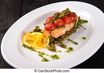 Grilled trout with tomatos leguminous beans and lemon on white plate. close up