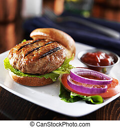 grilled turkey burger on bun with lettuce and fixings