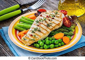 Grilled turkey fillet with vegetables on wooden background