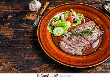 Grilled veal meat chop steak on a plate with salad. Dark wooden background. Top view. Copy space