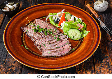 Grilled veal meat chop steak on a plate with salad. Dark wooden background. Top view