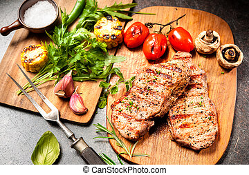 Grilled veal steaks on cutting board