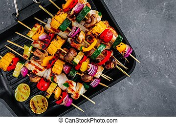 Grilled vegetable and chicken skewers on a grill pan, top view