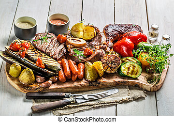 Grilled vegetables and steak with salt on white table