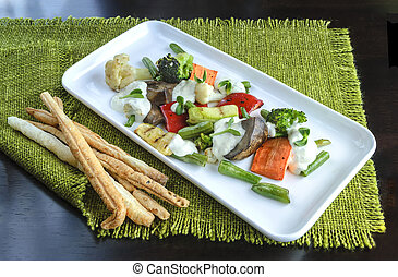 Grilled vegetables on a white plate, dark background