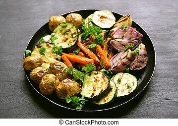 Grilled vegetables on dark plate.