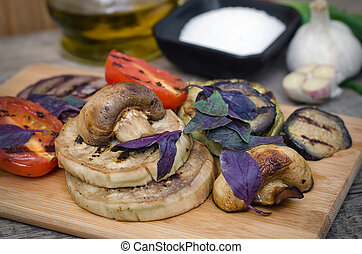 Grilled vegetables with basil on cutting board