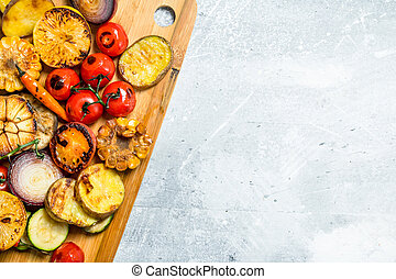 Grilled vegetables with spices and herbs on a cutting Board.