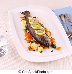 Grilled whole trout with vegetables and cutlery