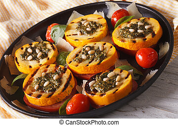 grilled zucchini and tomatoes with pesto, cheese and nuts closeup. Horizontal