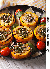 grilled zucchini and tomatoes with pesto, cheese and nuts closeup. vertical