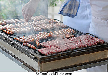 Grilling meat - Fresh meat on the grill with hand of cook