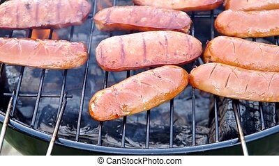 Grilling sausages on a grill outdoors in the garden
