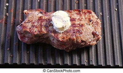 Grilling steak with a piece of melting butter