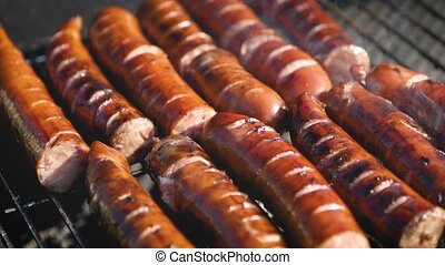 Grilling tasty sausages on barbecue grill. BBQ in the garden