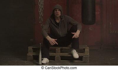 Grim hooligan in hoodie aggressively gesturing in industrial...
