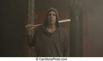 Grim looking hoodlum in hoodie holding baseball bat, walking...
