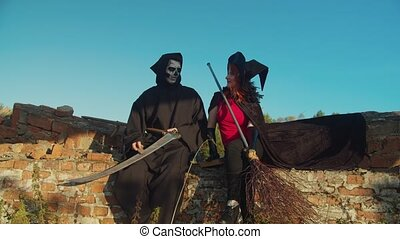 Spooky grim reaper sharpening scythe blade and black sorceress in black cloak with broom talking, planning evil deeds on halloween while devilry sitting on ruined parapet in rays of setting sun.