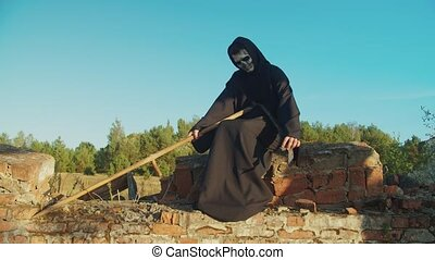 Creepy grim reaper, angel of death, in black cloak sitting on ruined breastwork, sharpening rustic scythe blade in rays of setting sun, ready for causing fear and haunting lost souls on halloween.