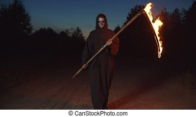 Spooky grim reaper in black cloak with burning scythe walking on dirt road in countryside at night, looking for lost souls, expressing fear, ruthlessness and horror during halloween holiday.