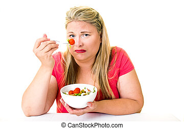 Grimacing overweight woman with bowl of salad - Grimacing...