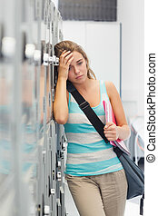 Grimacing pretty student having a headache in school
