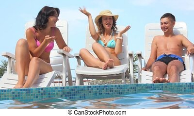 grimacing woman sits on deck chair near water pool, friends...