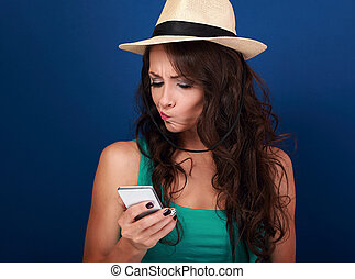 Grimacing young woman in hat looking on mobile phone with...