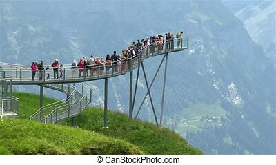 Tourists enjoy Swiss Alps panoramic views from the Grindelwald First viewing walkway.