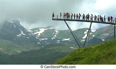 Tourists enjoys Swiss Alps panoramic views from the Grindelwald First viewing walkway.
