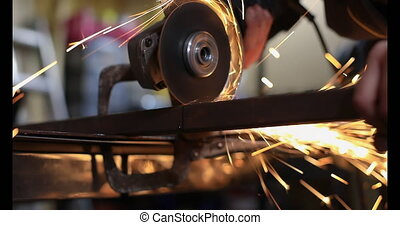 Selective focus of young woman, using grinding machine to cut metal rod pipes in pieces with firm hold using clamp as per requirement on workspace