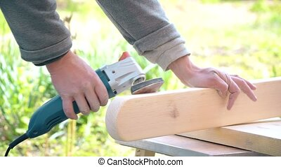 Grinding a wooden pine plank with an orbital detail sander...