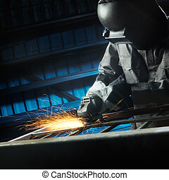 grinding after weld - man grinding in workshop with safety...