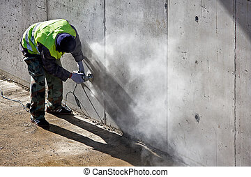 Worker grinds concrete wall on the site