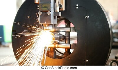 Grinding machine is cutting the pipe and a lot of sparks flying.