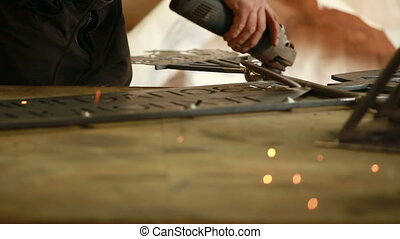 grinding machine sparks - man working by grinding machine...